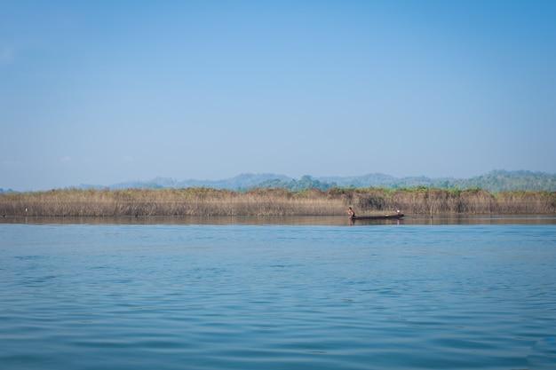 Hombre pescador en un barco en un hermoso río y montaña