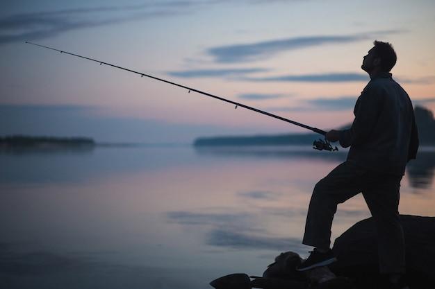 Hombre pescador pescando con varilla giratoria en la orilla de un río en el brumoso atardecer brumoso.
