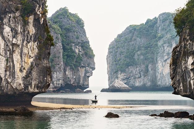 Hombre pescando en un bote entre montañas en la bahía de halong