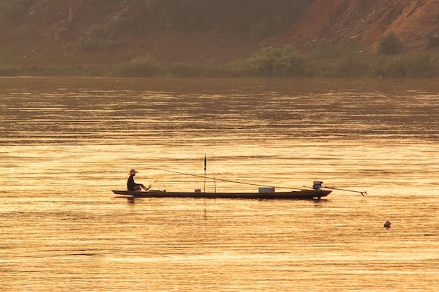 El hombre pescando en un campo en la temporada de inundaciones.