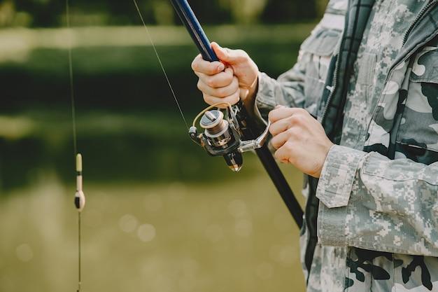 Hombre pescando y sostiene la caña de pescar
