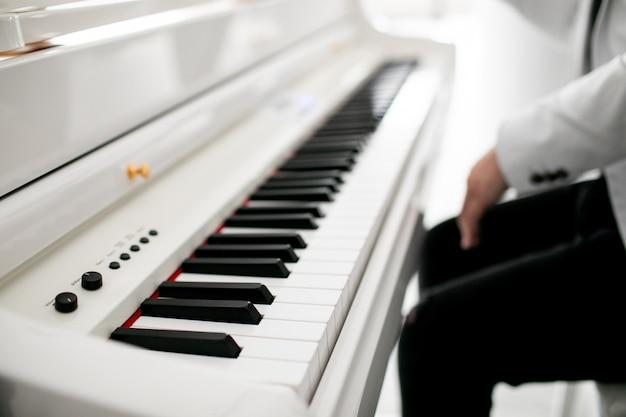 Hombre pianista manos en el teclado del piano de cola