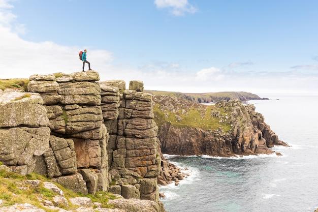 Hombre de pie en un acantilado de roca disfrutando de la vista