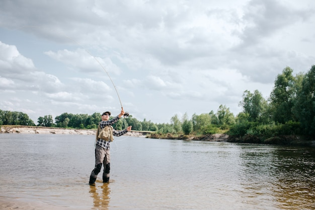 Hombre de pie en el agua y saludando con caña. él lo sostiene con ambas manos. guy está mirando la caña de pescar. lleva gafas de sol, chaleco y zancudas.