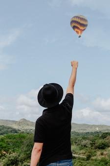 Hombre de pie con el brazo y el puño levantados en el aire y un globo aerostático volando al fondo