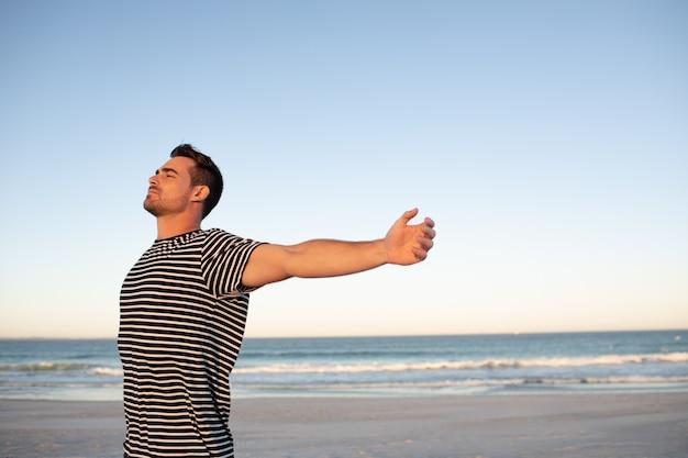 Hombre de pie con los brazos extendidos en la playa