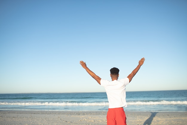 Hombre de pie con los brazos en la playa