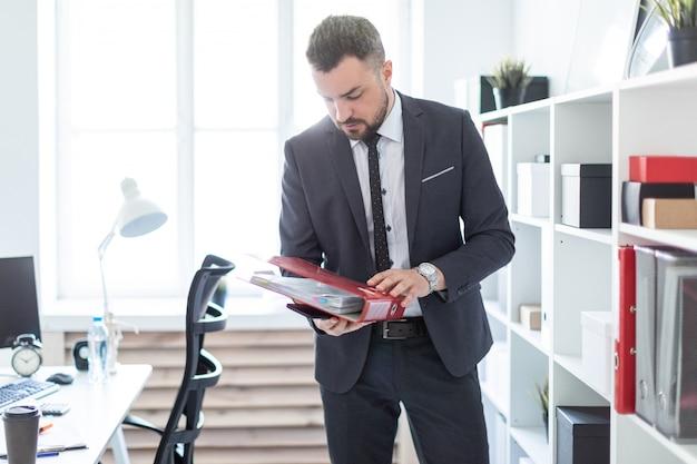 El hombre está de pie cerca del estante de la oficina y sostiene una carpeta.