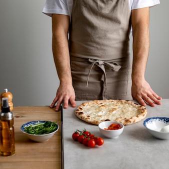 Hombre de pie cerca de la masa de pizza al horno con ingredientes
