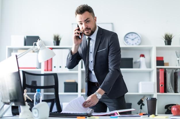 Un hombre está de pie cerca de una mesa en la oficina, hablando por teléfono y hojeando documentos.