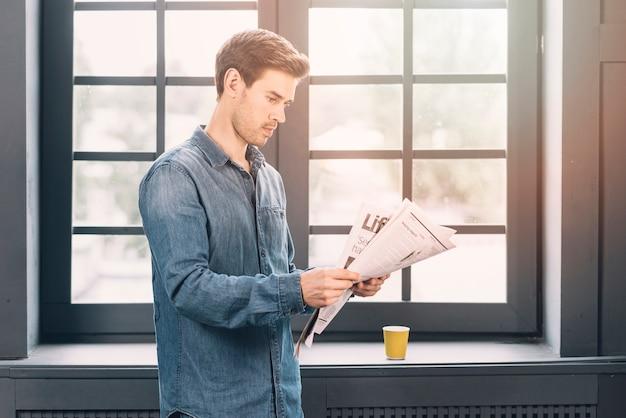 Un hombre de pie cerca de la ventana cerrada leyendo el periódico