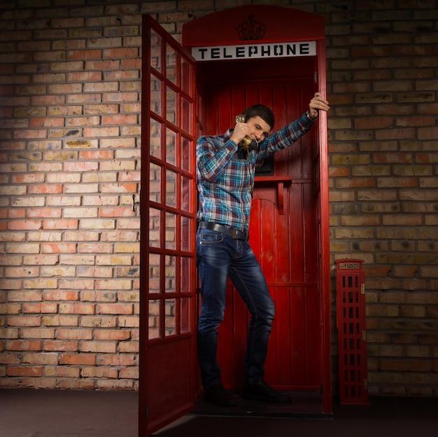 Hombre de pie charlando en una réplica de la cabina telefónica británica roja de pie apoyado contra la puerta abierta, vista de longitud completa