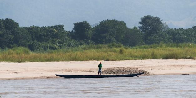 Hombre de pie en la costa del río mekong, lai ngao, distrito de wiang kaen, provincia de chiang rai, thail