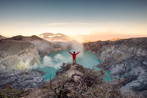 Hombre de pie en la cresta del cráter al amanecer por la mañana