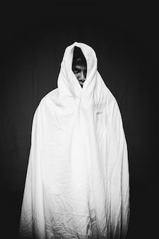 Hombre de pie, cubierta de tela blanca, fondo negro, concepto de halloween