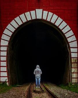 Hombre de pie delante del túnel ferroviario
