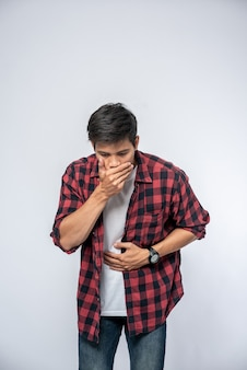Un hombre de pie con dolor de estómago ponga sus manos sobre su estómago y cubra su boca.