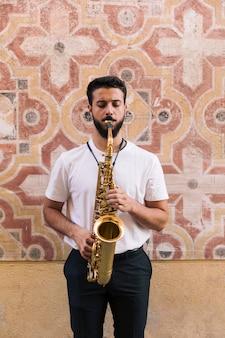 Hombre de pie y de frente tocando el saxofón sobre un fondo geométrico