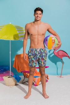 Hombre de pie joven en traje de baño sosteniendo la bola inflable