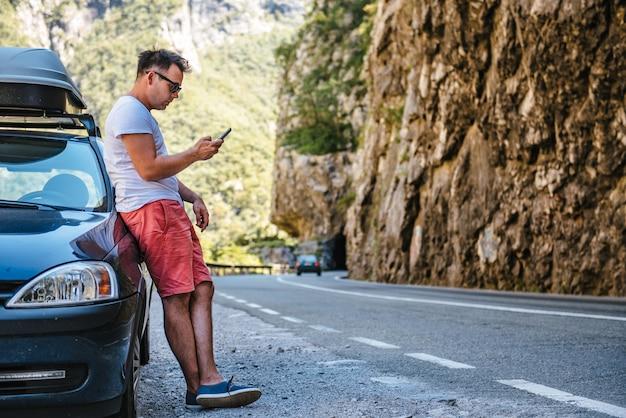 Hombre de pie junto al auto broke down y usando un teléfono inteligente