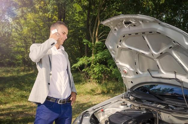 Hombre de pie junto al capó abierto haciendo una llamada telefónica y tratando de arreglar el vehículo