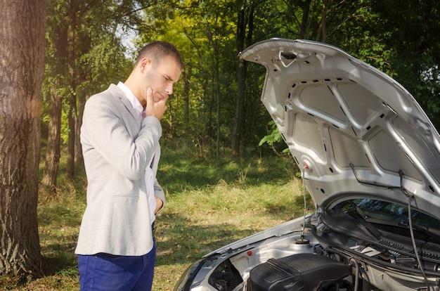 Hombre de pie junto al capó abierto tratando de arreglar el vehículo