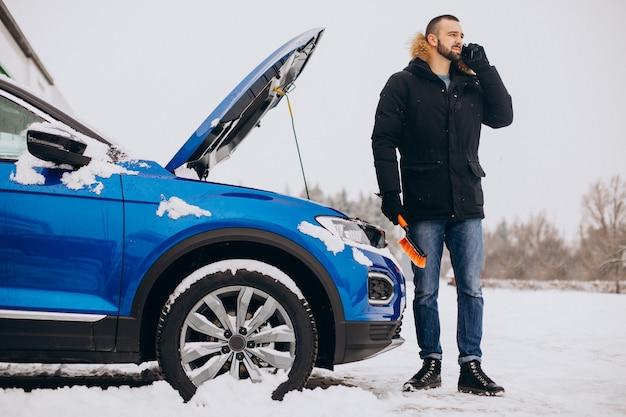 Hombre de pie junto al coche roto y pidiendo ayuda