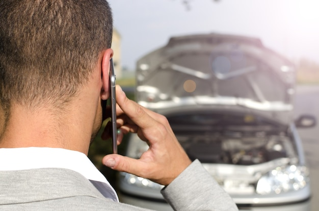Hombre de pie junto al vehículo roto llamando al servicio de remolque