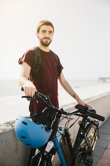 Hombre de pie junto a la bicicleta eléctrica y mirando a la cámara