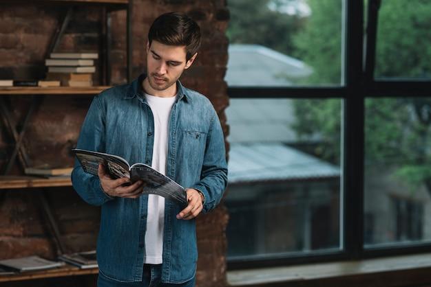 Hombre de pie junto a la estantería leyendo revista.