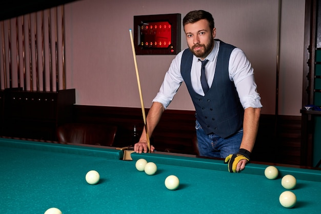 Hombre de pie junto a la mesa de billar, posando, con ropa formal. retrato