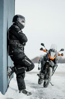 Hombre de pie junto a la motocicleta con casco