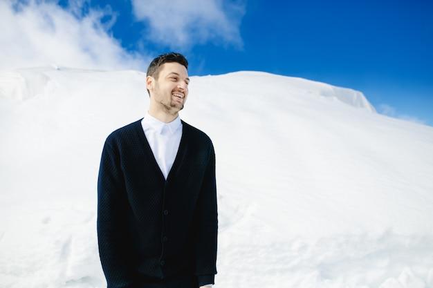 Hombre de pie en la ladera de la montaña nevada