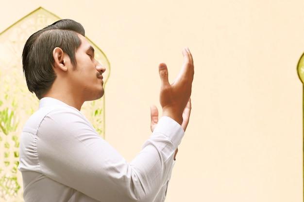 Hombre de pie mientras levanta las manos y reza en la mezquita.