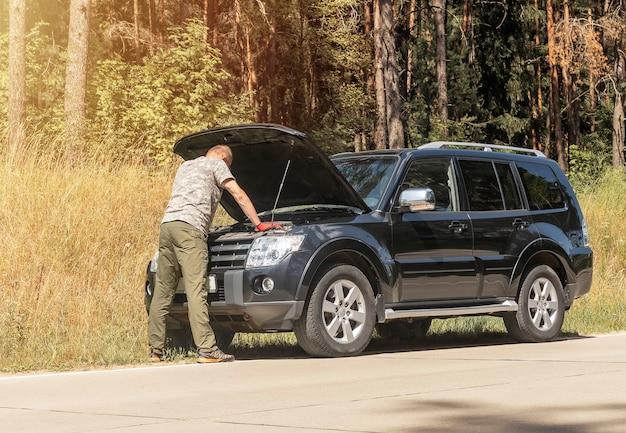 Hombre de pie y mirando en el capó levantado y pensando en el problema después de la rotura del coche