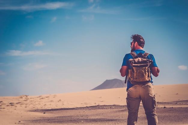 Hombre de pie con mochila y desierto