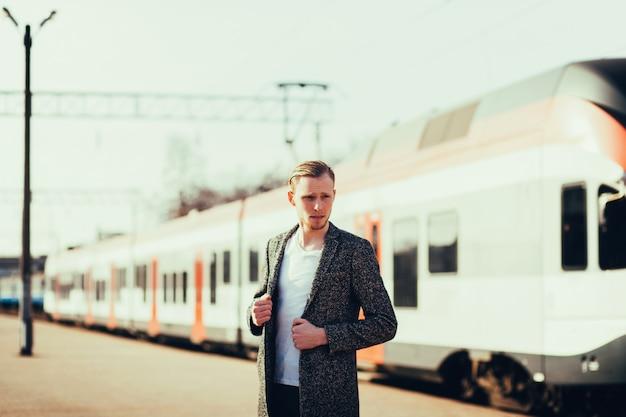 Hombre de pie en una moderna estación de tren