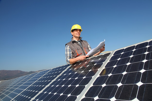 Hombre de pie por paneles solares con plano de construcción.