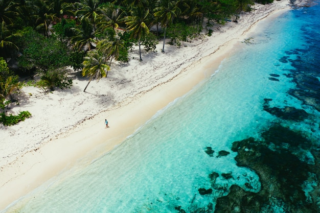 Hombre de pie en la playa y disfrutar del lugar tropical con vistas. colores del mar caribe y palmeras. concepto sobre viajes y estilo de vida.
