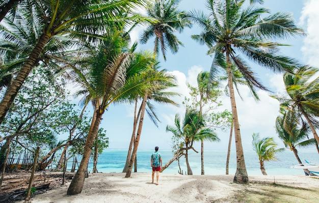 Hombre de pie en la playa y disfrutar del lugar tropical con vistas. colores del mar caribe y palmeras en el fondo. concepto sobre viajes y estilo de vida.