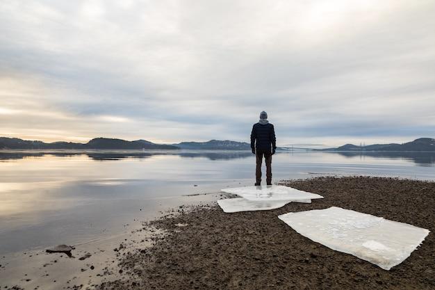 Hombre de pie en la playa, témpanos de hielo sobre arena oscura, mar en calma, niebla y niebla. hamresanden, kristiansand, noruega