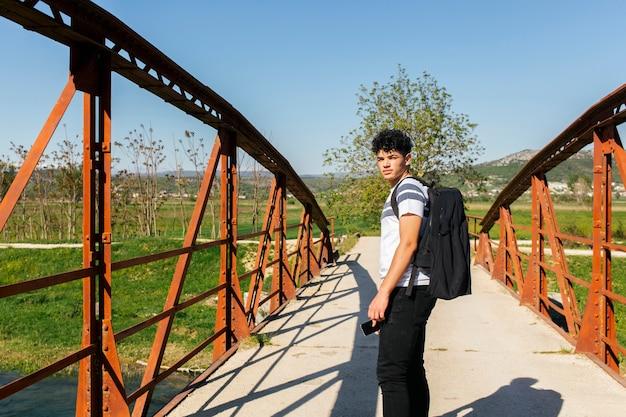 Hombre de pie en el puente mirando a la cámara con teléfono móvil