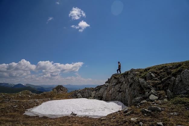 Un hombre de pie sobre las rocas delante del fondo del cielo
