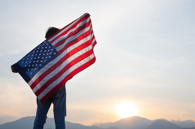 Hombre de pie y sosteniendo la bandera de estados unidos en la vista del amanecer
