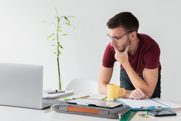 Hombre de pie en su escritorio y mirando a otro lado