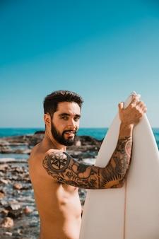 Hombre de pie con tabla de surf blanca en la playa