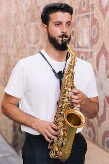 Hombre de pie tocando el saxofón sobre fondo geométrico