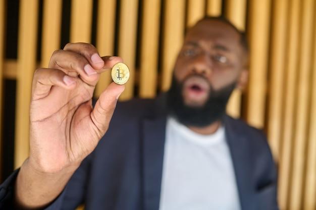 Un hombre de piel oscura con barba sosteniendo un bitcoin.