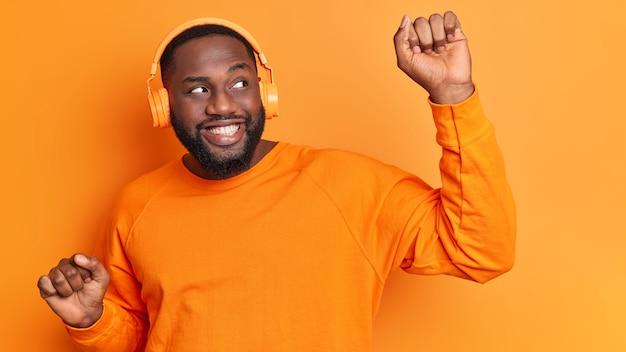 Hombre de piel oscura barbudo despreocupado positivo sonríe ampliamente levanta los brazos