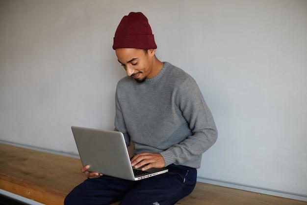Hombre de piel oscura barbudo joven de aspecto agradable con suéter gris, pantalón azul y gorra burdeos sentado sobre una pared blanca y charlando con sus amigos en su computadora portátil